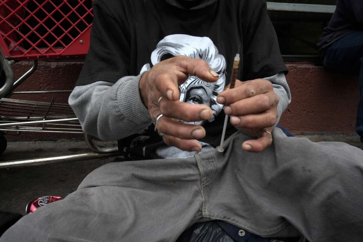 Drug addict prepares a needle to inject himself with heroin in front of a church in the Skid Row area of Los Angeles.