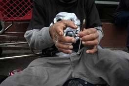 "In this Monday, May 6, 2013 file photo, a drug addict prepares a needle to inject himself with heroin in front of a church in the Skid Row area of Los Angeles. It's not a rare scene on Skid Row to spot addicts using drugs in the open, even when police patrol the area. Jim Hall, an epidemiologist who studies substance abuse at Nova Southeastern University in Fort Lauderdale, Fla. says, the striking thing about heroin's most recent incarnation in the early 21st Century, is that a drug that was once largely confined to major cities is spreading into suburban and rural towns across America, where it is used predominantly by young adults between the ages of 18 and 29. ""We haven't really seen something this rapid since probably the spread of cocaine and crack in the mid-1980s,"" Hall said. (AP Photo/Jae C. Hong)"