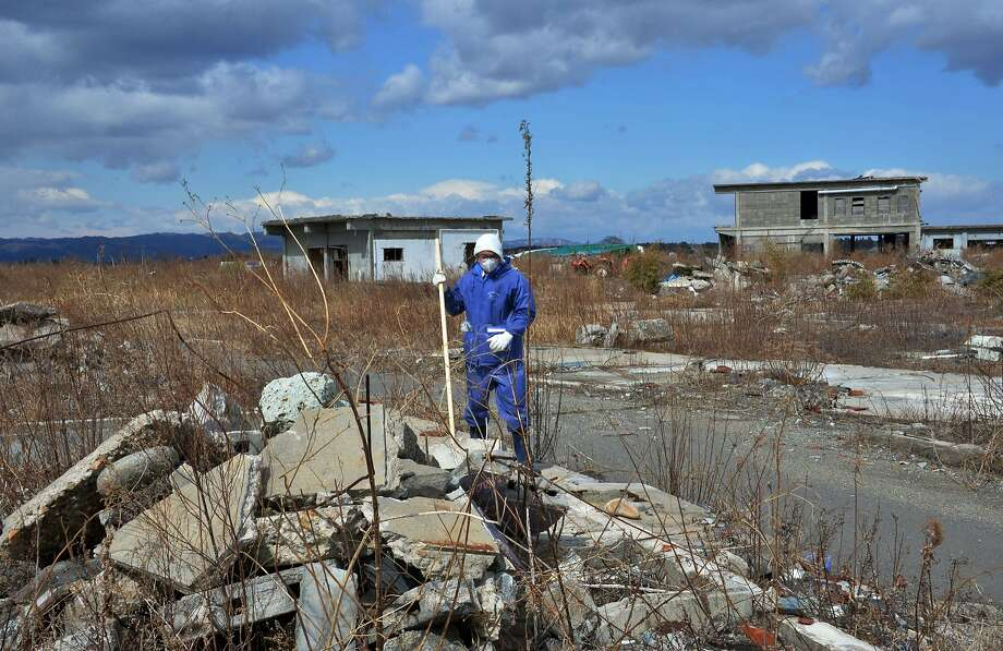 A tsunami survivor searches for the remains of missing people at Namie, near the striken TEPCO's Fukushima Dai-ichi nuclear plant in Fukushima prefecture on March 11, 2014 on the third anniversary day of massive earthquake and tsunami hit northern Japan. The 9.0 magnitude earthquake in 2011 sent a huge wall of water into the coast of the Tohoku region, splintering whole communities, ruining swathes of prime farmland and killing nearly 19,000 people. Photo: Yoshikazu Tsuno, AFP/Getty Images
