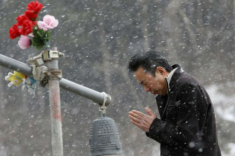 A man offers prayers in front of the main entrance of Okawa Elementary School where 74 of the 108 students went missing after the March 11, 2011 tsunami in Ishinomaki, Miyagi prefecture, northern Japan, Tuesday, March 11, 2014. Photo: Shizuo Kambayashi, Associated Press