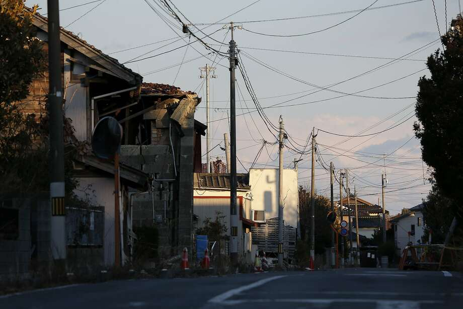 Telephone poles and damaged houses stand along a road in an area damaged by the tsunami following the March 2011 earthquake in Namie, Fukushima Prefecture, Japan, on Monday, March 10, 2014. March 11 marks three years since Japan's deadliest earthquake in 2011, a magnitude-9 temblor that triggered a tsunami in northeastern Japan, leaving about 19,000 people dead or missing and hundreds of thousands homeless as it wiped out entire towns.  Photo: Kiyoshi Ota, Bloomberg