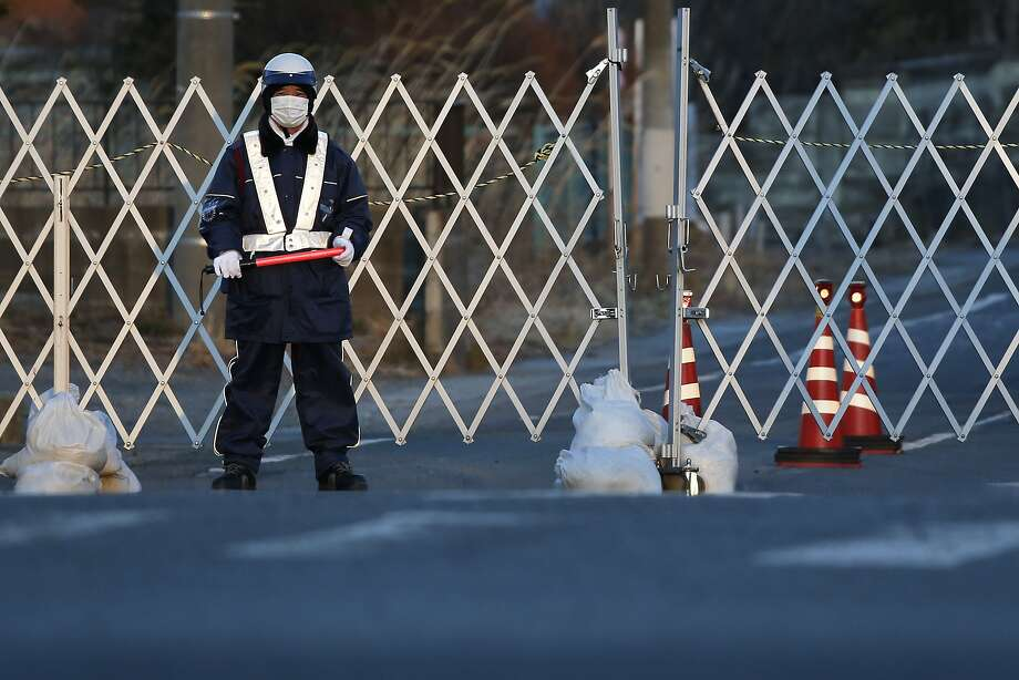 A security officer guards a gate to a restricted area in Namie, Fukushima Prefecture, Japan, on Monday, March 10, 2014. March 11 marks three years since Japan's deadliest earthquake in 2011, a magnitude-9 temblor that triggered a tsunami in northeastern Japan, leaving about 19,000 people dead or missing and hundreds of thousands homeless as it wiped out entire towns. Photo: Kiyoshi Ota, Bloomberg