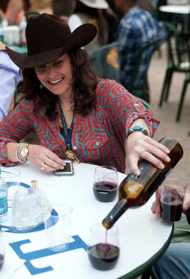 Mandy Jackson pours a glass of wine at the Champion Wine Garden. Wine has become a popular draw at the rodeo, with big crowds gathering at Carruth Plaza on weekend evenings. Photo: J. Patric Schneider, Freelance / © 2014 Houston Chronicle
