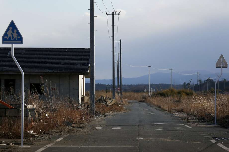 Telephone poles and crossing signs stand along a road in an area damaged by the tsunami following the March 2011 earthquake in Namie, Fukushima Prefecture, Japan, on Monday, March 10, 2014. March 11 marks three years since Japan's deadliest earthquake in 2011, a magnitude-9 temblor that triggered a tsunami in northeastern Japan, leaving about 19,000 people dead or missing and hundreds of thousands homeless as it wiped out entire towns. Photo: Kiyoshi Ota, Bloomberg