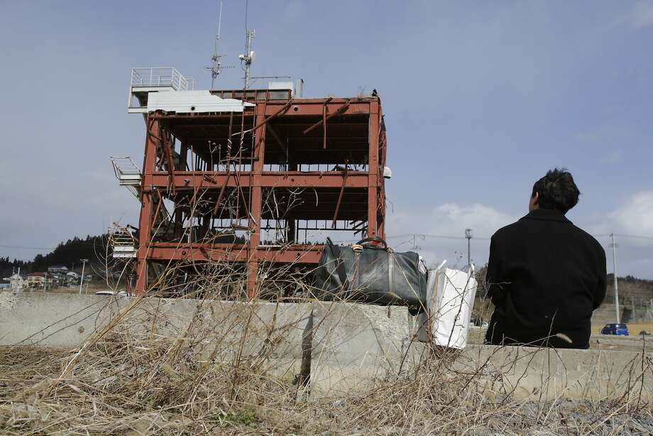 A man sits in front of what is left of a disaster control center in an area devastated by the March 11, 2011 earthquake and tsunami, in Minamisanriku, Miyagi Prefecture, northern Japan, Tuesday, March 11, 2014. Japan marked the third anniversary on Tuesday of a devastating disasters that left nearly 19,000 people dead or missing. Photo: Shizuo Kambayashi, Associated Press