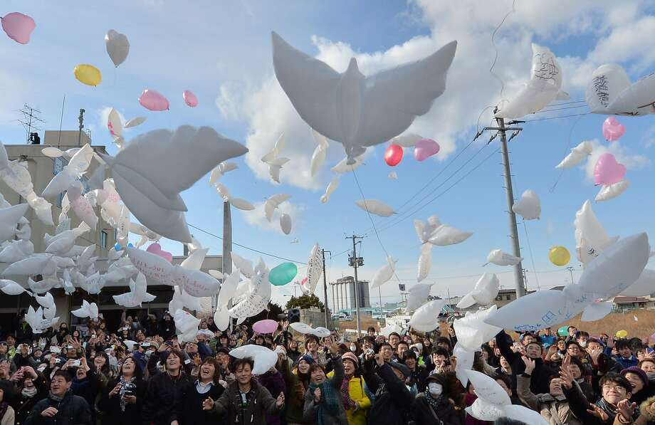 Balloons in the shape of doves are released into the air during a memorial service for tsunami victims at the former Yuriage junior high school in Natori, Miyagi Prefecture on March 11, 2014 on the third anniversary of the massive earthquake and tsunami that hit northern Japan. The 9.0 magnitude earthquake in 2011 sent a huge wall of water into the coast of the Tohoku region, splintering whole communities, ruining swathes of prime farmland and killing nearly 19,000 people.  Photo: Kazuhiro Nogi, AFP/Getty Images