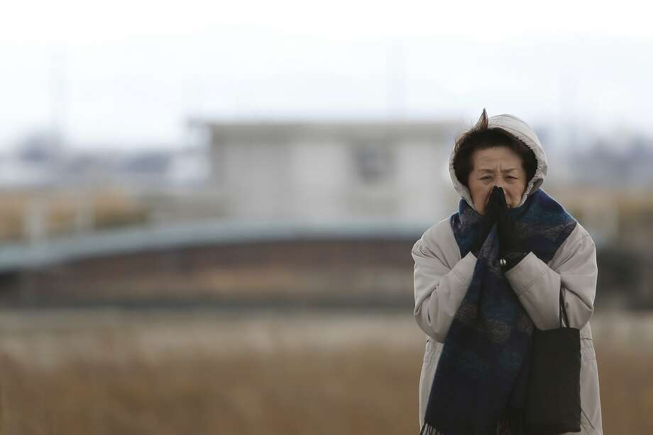 A woman prays on the third anniversary of the Great East Japan Earthquake and Tsunami in an area damaged by the disaster in Sendai, Miyagi Prefecture, Japan, on Tuesday, March 11, 2014. Today marks three years since Japan's deadliest earthquake in 2011, a magnitude-9 temblor that triggered a tsunami in northeastern Japan, leaving about 19,000 people dead or missing and hundreds of thousands homeless as it wiped out entire towns.  Photo: Kiyoshi Ota, Bloomberg