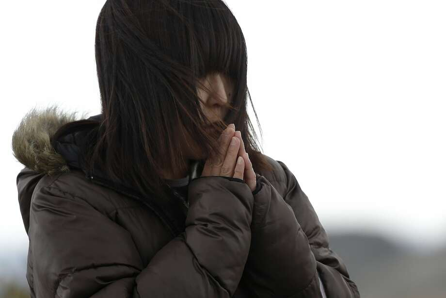 A woman prays on the third anniversary of the Great East Japan Earthquake and Tsunami near a coast damaged by the disaster in Sendai, Miyagi Prefecture, Japan, on Tuesday, March 11, 2014. Today marks three years since Japan's deadliest earthquake in 2011, a magnitude-9 temblor that triggered a tsunami in northeastern Japan, leaving about 19,000 people dead or missing and hundreds of thousands homeless as it wiped out entire towns. Photo: Kiyoshi Ota, Bloomberg