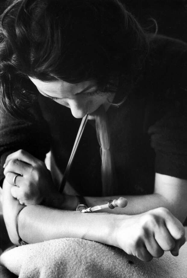 "Karen, a drug addict w. nylon stocking around her arm to make vein pop out as she uses hypodermic needle on an eyedropper which addicts call a ""spike"" to shoot up w. heroin.  (Photo by Bill Eppridge/Time & Life Pictures/Getty Images) Photo: Bill Eppridge, Time Life Pictures/Getty Images"