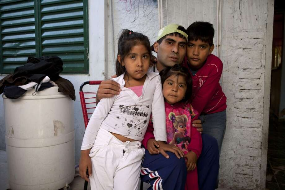 "Cristian Marcelo Reynoso, center, poses inside his home with his children, Milagro, 5, left, Oriana, 3, bottom, and Nahuel, 10, right, in their home in the Villa 21-24 slum in Buenos Aires, Argentina, Thursday, March 14, 2013.  At Villa 21-24, a slum so dangerous that most outsiders wouldn't dare go in, Jorge Mario Bergoglio often showed up unannounced to share laughs and sips of mate, the traditional Argentine herbal tea. Reynoso, 27, said their favorite soccer club, San Lorenzo, ""was going through a bad streak the last time they talked, and he told me that even if it was losing you couldn't desert it ... It's like people. We all hit the bottom of the well, but you can always be rescued from the bottom."" Reynoso is trying to kick off an addiction to crack cocaine through the local church's rehab program. (AP Photo/Victor R. Caivano) Photo: Victor R. Caivano, Associated Press"