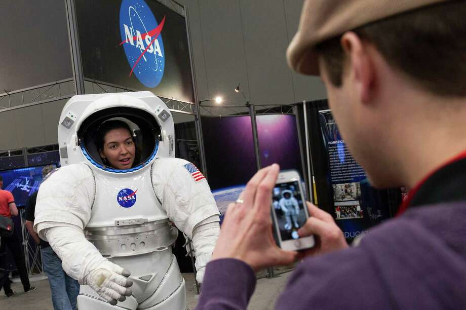 An attendee poses for a photograph in a National Aeronautics and Space Administration (NASA) space suit at the South By Southwest (SXSW) Interactive Festival in Austin, Texas, U.S., on Monday, March 10, 2014. The SXSW conferences and festivals converge original music, independent films, and emerging technologies while fostering creative and professional growth. Photographer: David Paul Morris/Bloomberg Photo: David Paul Morris, Bloomberg / © 2014 Bloomberg Finance LP