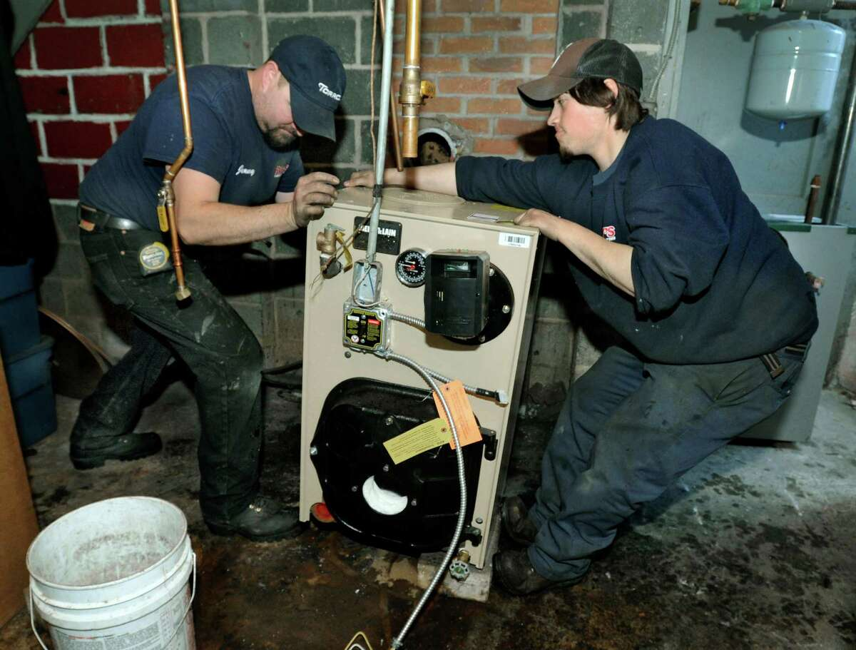 Jim Devendorf, 42, of New Milford, Conn., left, and Ian Hripak, 20, of Sandy Hook, install a new furnace in a home at the Mill Ridge housing developement in Danbury, Conn. Tuesday, March 11, 2014.
