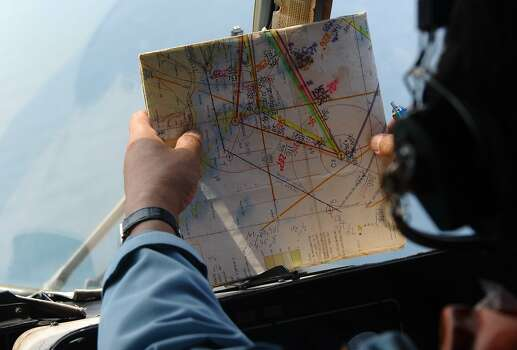 A crew member checks the map March 11, 2014, while searching aboard a Vietnamese Air Force Russian-made MI-171 helicopter. Photo: Hoang Dinh Nam, AFP/Getty Images