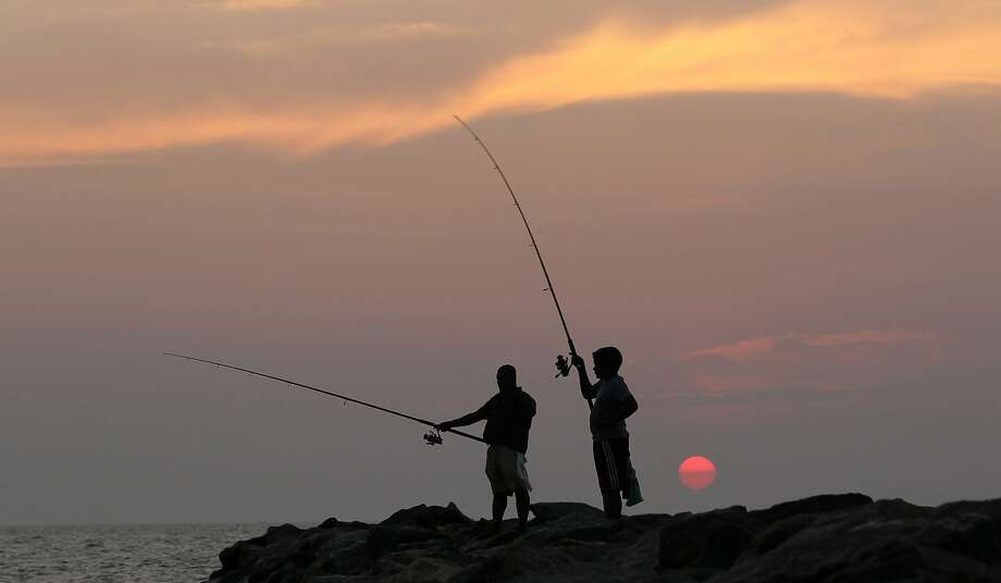 A nation of fishermen: A Sri Lankan man and boy fish as the sun sets over the Indian Ocean in Colombo. More than 600,000 people on the island country depend on fishing or related industries for their 