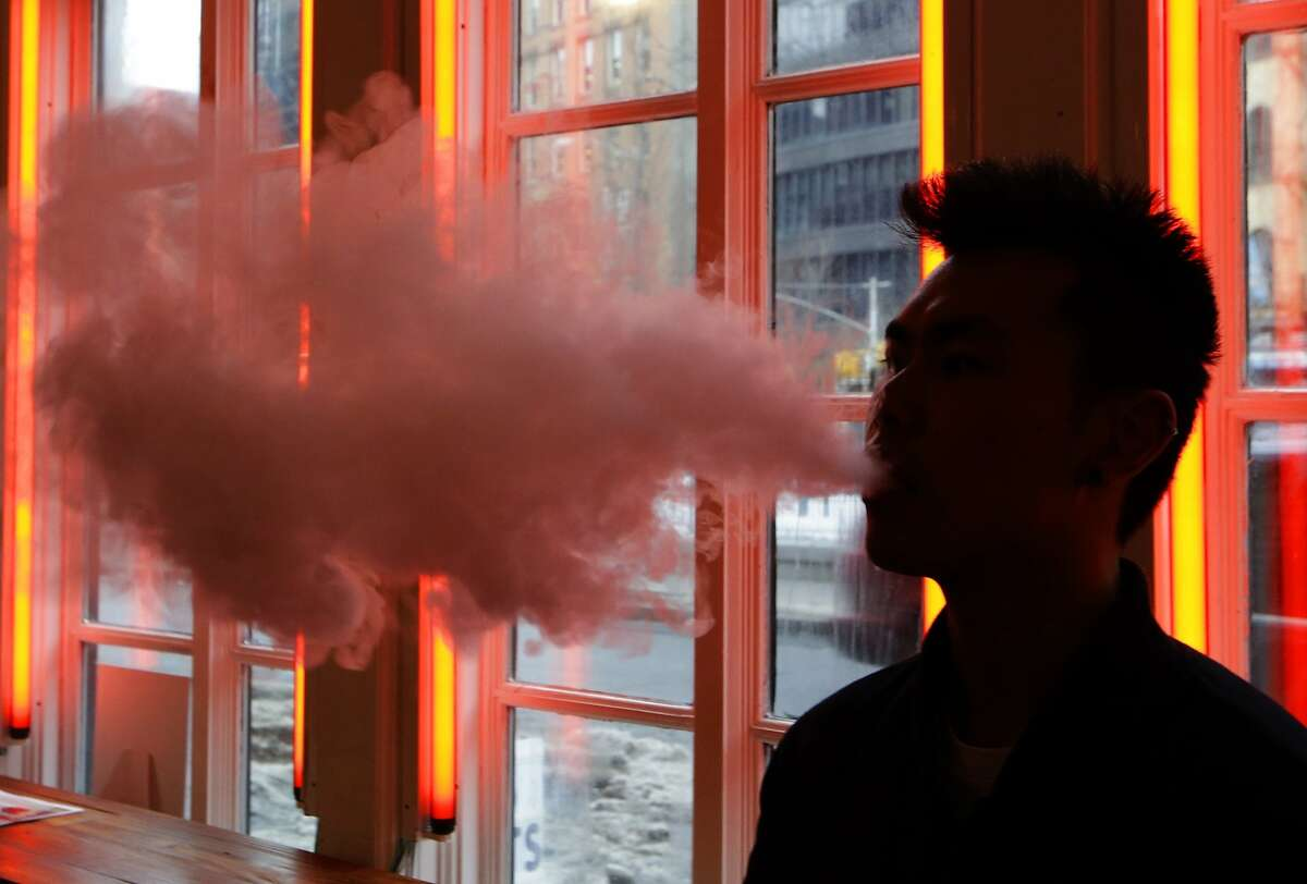 In this Feb. 20, 2014 photo, a patron exhales vapor from an e-cigarette at the Henley Vaporium in New York. The proprietors are peddling e-cigarettes to