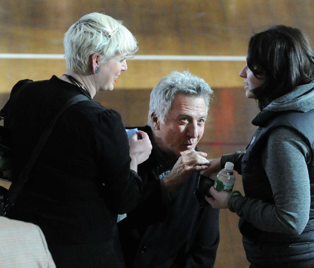 Actor Dustin Hoffman, center, takes a drink of a beverage on the set of