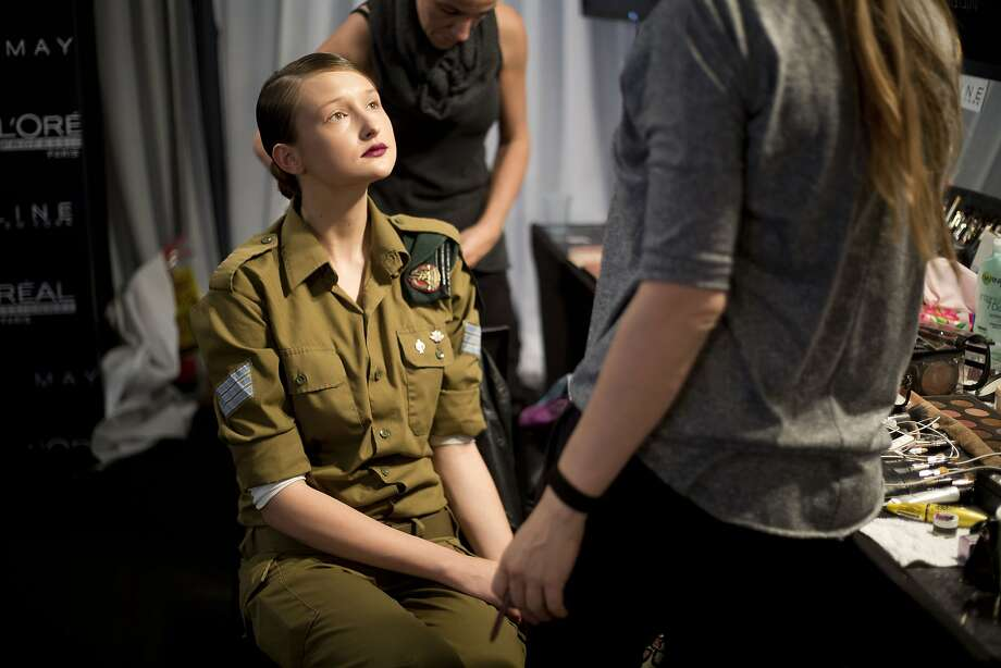 Olive drab is the new black: An Israeli model who serves in the military sits for a makeup session before her turn on the catwalk during a show by Israeli designer Dorin Frankfurt at Tel Aviv Fashion Week. Photo: Ariel Schalit, Associated Press
