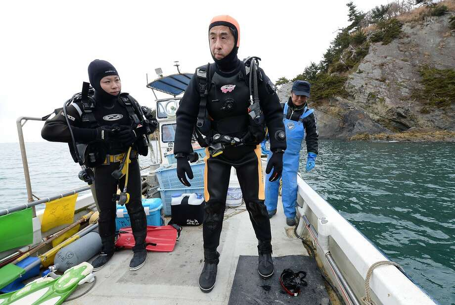 Yasuo Takamatsu (center) and an instructor head for a diving spot in Miyagi Prefecture. The 57-year-old bus driver started scuba lessons in November in hopes of finding his missing spouse. Photo: Toru Yamanaka, AFP/Getty Images