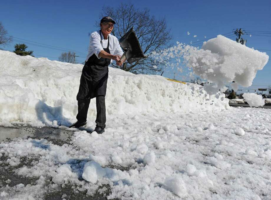 Hana employee Tin Chen makes parking spaces more accessible by shoveling snow from large snowbanks onto the pavement to melt in the warm weather on Tuesday, March 11, 2014, in Guilderland, N.Y.  (Lori Van Buren / Times Union) Photo: Lori Van Buren / 00026098A