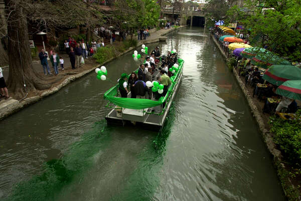 A river boat carrying dignitaries and the San Antonio Pipe and Drums drops green dye into the San Antonio River during the St. Patrick's Day Dyeing of the River Green press conference Saturday, March 16, 2002 Kangaroo Court. BAHRAM MARK SOBHANI/STAFF