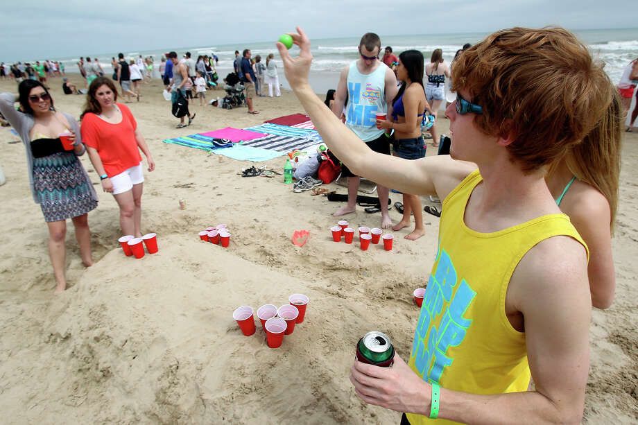 Chase Kaiser, of College Station, plays beer pong during Spring Break on a South Padre Island beach. Photo: Tom Reel, San Antonio Express-News