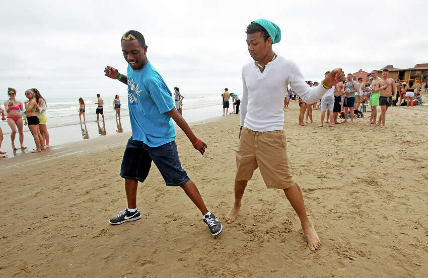 Darius Tanner (left) and J.T. Oby, both from College Station, practice a dance move in the sand during Spring Break 2014 on the South Padre Island beach near Clayton's on March 11, 2014.