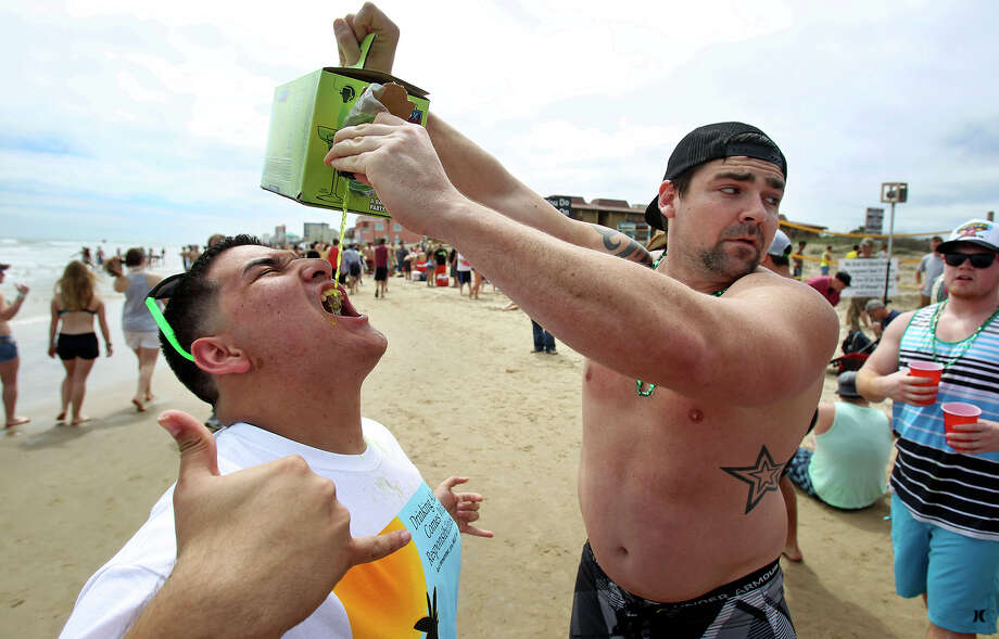 Joseph Hurst does the honors for Omar Rodriguez who swallows a sample of liquid along the beach during Spring Break 2014 on the South Padre Island beach near Clayton's  on March 11, 2014. Photo: Tom Reel, Express-News