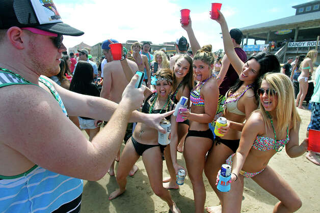 Jeff Heinzer, from College Station, grabs a picture of his friends during Spring Break 2014 on the South Padre Island beach near Clayton's  on March 11, 2014. Photo: TOM REEL
