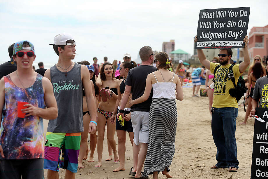 Pastor Dan Sem, from the Sovereign Grace Community Church holds a sign amidst the chaos during Spring Break 2014 on the South Padre Island beach near Clayton's  on March 11, 2014. Photo: TOM REEL