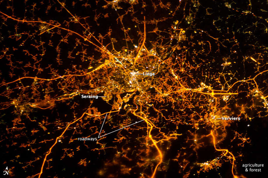 "Category: Photograph Section. To paraphrase an old expression: ""all roads lead to Liège."" Or at least you could get that impression from this astronaut photograph. The brightly lit core of the Liège urban area appears to lie at the center of a network of roadways—traceable by continuous orange lighting extending out into the rural and relatively dark Belgian countryside. For a sense of scale, the distance from image left to right is approximately 70 kilometers (43 miles). The region to the southeast of Verviers includes agricultural fields and forest; hence, it appears almost uniformly dark at night."