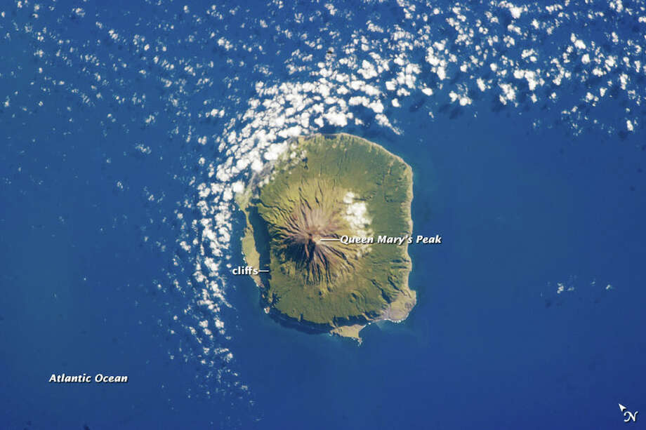 Category: Photograph Section. The island of Tristan da Cunha is located in the southern Atlantic Ocean—more than 3,700 kilometers (2,300 miles) from the coastline of Antarctica, approximately 2,800 kilometers (1,700 miles) to the southern tip of Africa, and more than 3,000 kilometers (1,900 miles) from the east coast of South America. The island forms part of the British Overseas Territory of Saint Helena, Ascension, and Tristan da Cunha. The shoreline of the 13 kilometer (8 mile) wide island is marked on most sides by steep cliffs, with lower beach areas on the southern and north-northwestern sides. The island is notable for its bird population and includes important breeding grounds for petrels, albatrosses, penguins, and shearwaters.