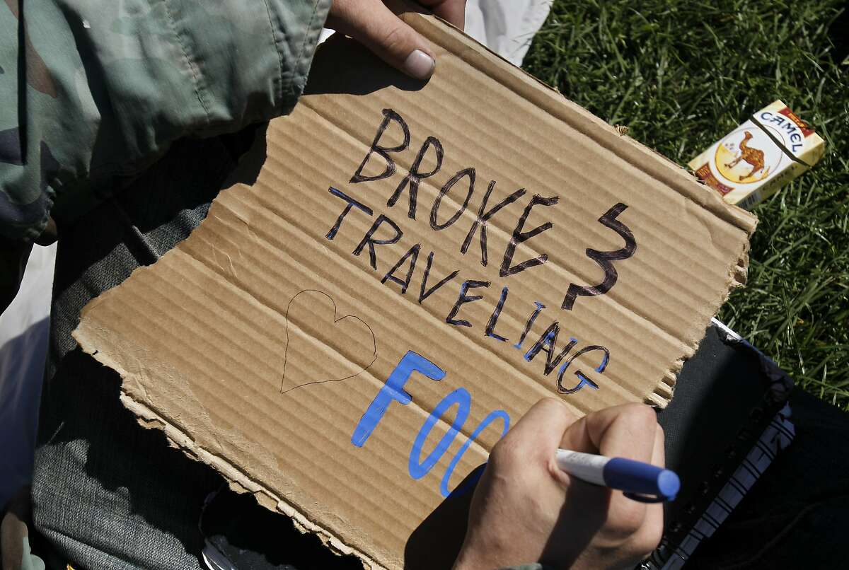 A young California traveler works on his panhandling sign in Golden Gate park Tuesday March 11, 2014. The 2013 San Francisco homeless census included a new separate daytime count of homeless children and youth which totaled an extra 914 homeless people that year.