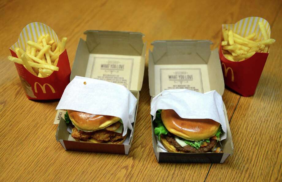 The premium Grilled Chicken Bacon Clubhouse, left, and the Bacon Clubhouse Burger, right, are two new sandwiches from McDonald's Tuesday, March 11, 2014, at the Times Union in Colonie, N.Y. (Will Waldron/Times Union) Photo: WW