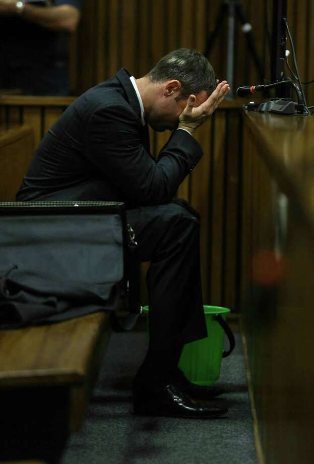 With a bucket on the floor nearby, Oscar Pistorius covers his face with his hands as he listens to cross questioning about the events surrounding the shooting death of his girlfriend Reeva Steenkamp, in court during his trial in Pretoria, South Africa, Tuesday, March 11, 2014. Pistorius is charged with the shooting death of Steenkamp, on Valentines Day in 2013. (AP Photo/Kevin Sutherland, Pool) Photo: Kevin Sutherland, POOL / POOL Times Media Group