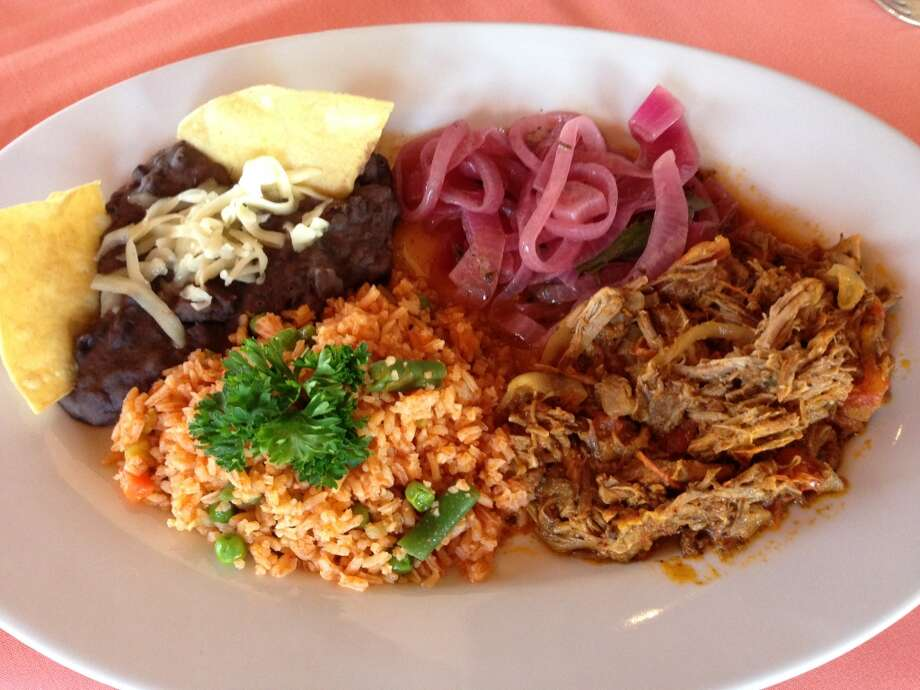 Cochinita pibil: Achiote-marinated pork baked in banana leaves served with pickled red onions, rice and refried black beans. (Photo: Greg Morago)