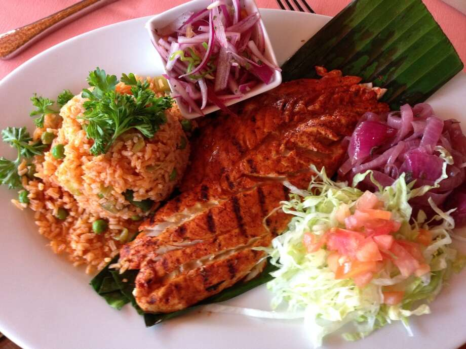 Huachinango Tikin-Xik: Red snapper filet basted with achiote sauce served with shredded cabbage, pickled red onions and Mexican rice. (Photo: Greg Morago)