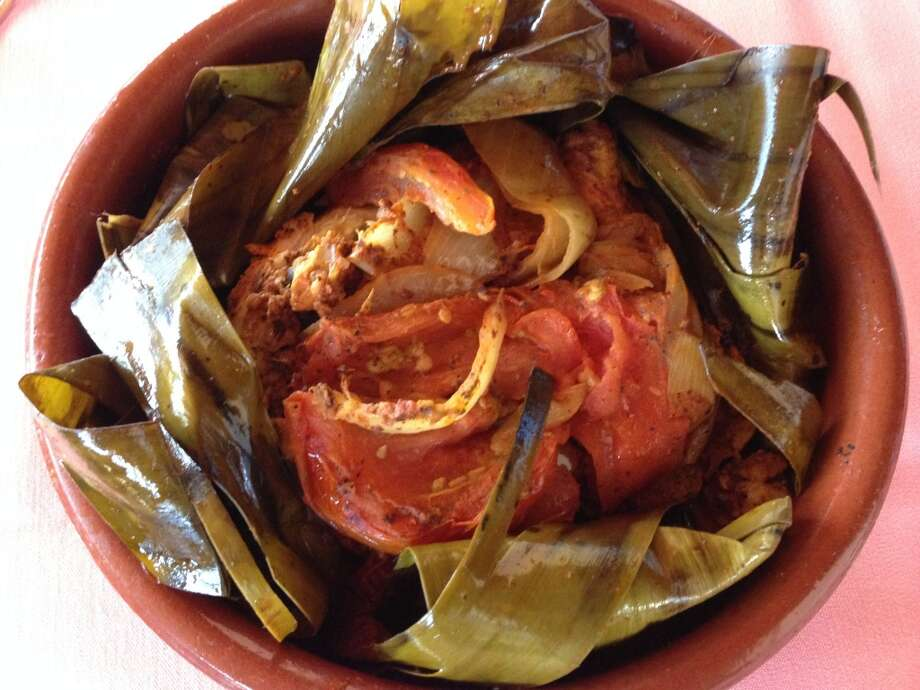 Pollo pibil: Achiote-marinated chicken baked in banana leaves. (Photo: Greg Morago)
