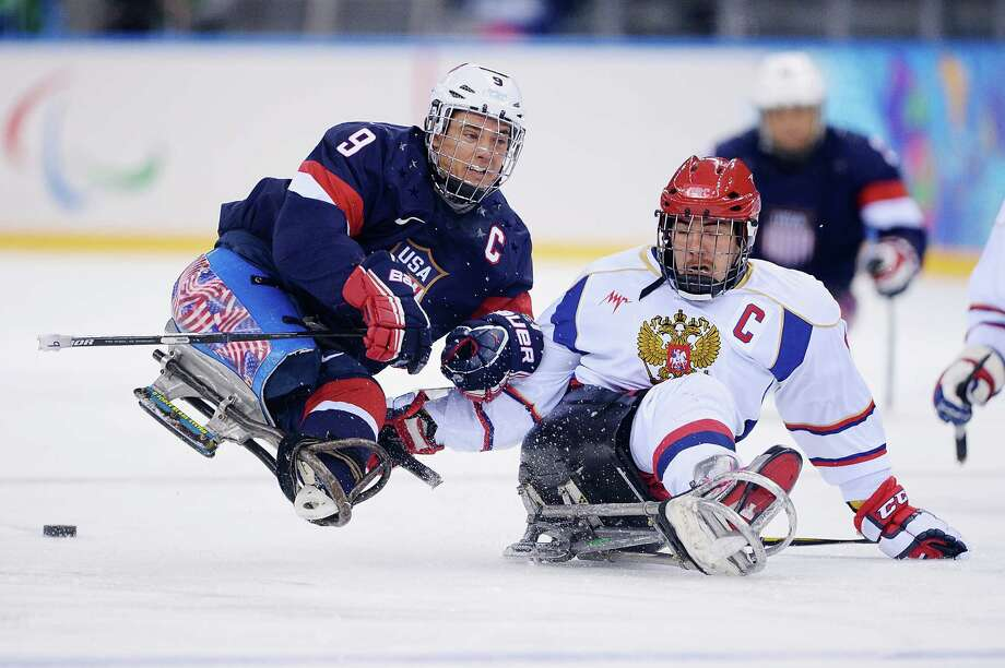 SOCHI, RUSSIA - MARCH 11:  Andy Yohe of the United States and Dmitrii Lisov of Russia battle for the puck during the Ice Sledge Hockey Preliminary Round Group B match between the United States of America and Russia during day four of Sochi 2014 Paralympic Winter Games at Shayba Arena on March 11, 2014 in Sochi, Russia. Photo: Dennis Grombkowski, Getty Images / 2014 Getty Images