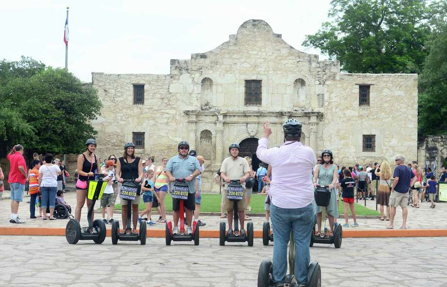 People riding Segway machines pose for a photograph in front of the Alamo on June 14, 2013 in San Antonio, Texas. The Alamo, built as a chapel after 1744,  is all that remains from the mission of San Antonio de Valero which was founded in 1718 by the Franciscans and eventually converted into a fortress. The city's most famous landmark played a crucial role in the Texas Revolution with the Battle of the Alamo, a thirteen day seige from February 23 to March 6, 1836, and remains a popular tourist destination.  AFP PHOTO/Frederic J. BROWNFREDERIC J. BROWN/AFP/Getty Images Photo: FREDERIC J. BROWN, Staff / AFP