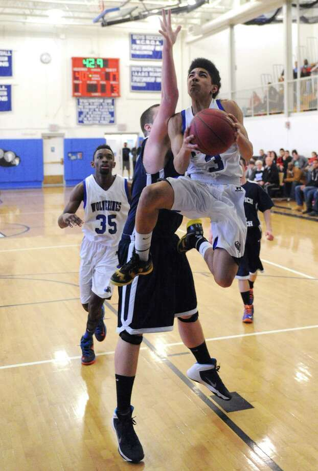 Abbott Tech's Nick Placella, right, attempts a layup past Norwich Tech defender Tom Nicholas in Abbott Tech's 79-44 win over Norwich Tech in the Class M high school boys basketball tournament first round game at Henry Abbott Technical High School in Danbury, Conn. on Tuesday, March 11, 2014. Photo: Tyler Sizemore / The News-Times