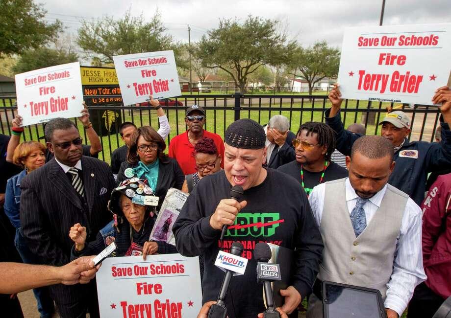 National Black United Front chairman Kofi Taharka leads protest chants outside Jones High School on Tuesday. Photo: Cody Duty, Staff / © 2014 Houston Chronicle