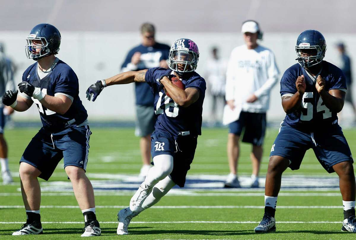 Rice Owls running back Brandon Hamilton (18) runs between Rice Owls offensive linesman Peter Godber (51)and Rice Owls offensive linesman Trey Martin (54) during Rice's first spring football practice on Tuesday, March 11, 2014. (Bob Levey/For The Chronicle)