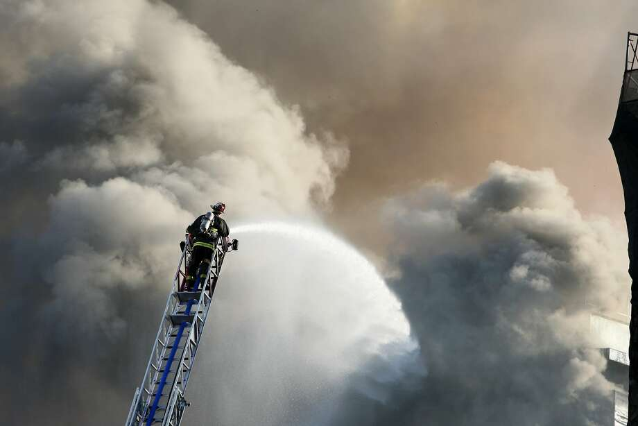 A firefighter at the top of a ladder sprays water into the fire as it rages in San Francisco, Calif. on March 11, 2014. Photo: Deborah Svoboda, The Chronicle