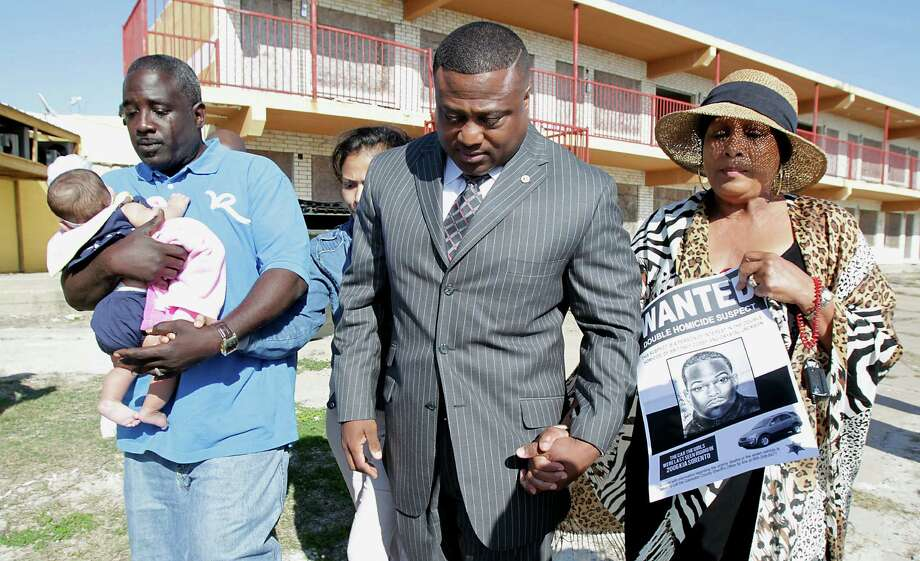 John Cooks, the uncle of Crystal Jackson, left, Victoria Rubio, partially obscured, Quanell X and Patricia  Nixon, the grandmother of Britney Cosby, attend a prayer vigil for the two slain young women. Photo: James Nielsen, Staff / © 2014  Houston Chronicle