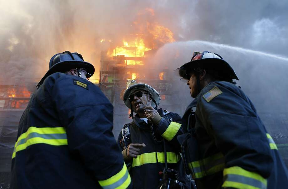 San Francisco Fire Battalion Chief McGee (center) directs the operation as firefighters battle a five alarm fire in the Mission Bay area of San Francisco, Calif. on Tuesday March 11, 2014. Photo: Michael Macor, The Chronicle