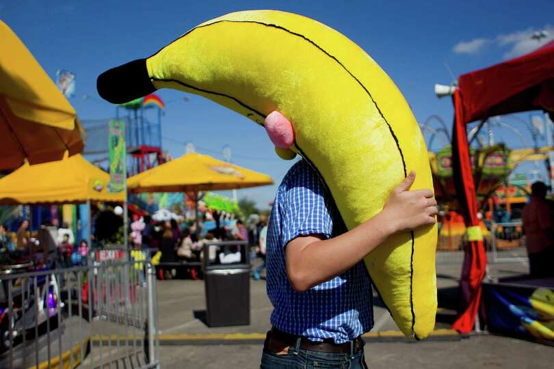 Luke Sterling, 13, of Crosby walks with a stuffed banana he won playing a game on the Houston Livest