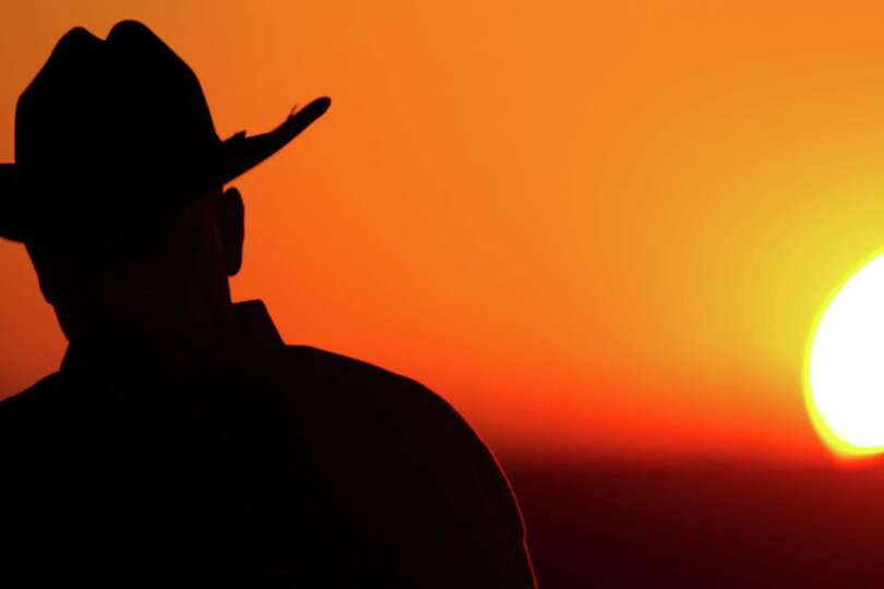 The sun sets as cowboys and cowgirls walked in to watch rodeo events during the second round of the