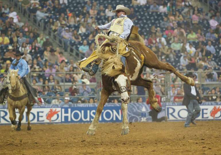 Chad Ferley hangs on during the Saddle Bronc Riding event after the second round of the Rodeo Housto