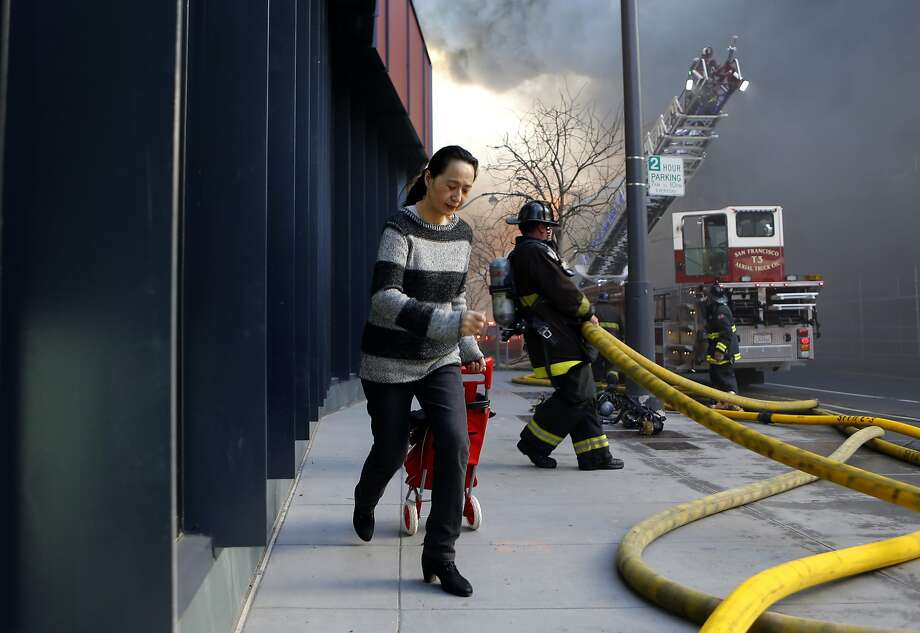 A resident evacuates the area as San Francisco firefighters battle a five alarm fire in the Mission Bay area of San Francisco, Calif. on Tuesday March 11, 2014. Photo: Michael Macor, The Chronicle