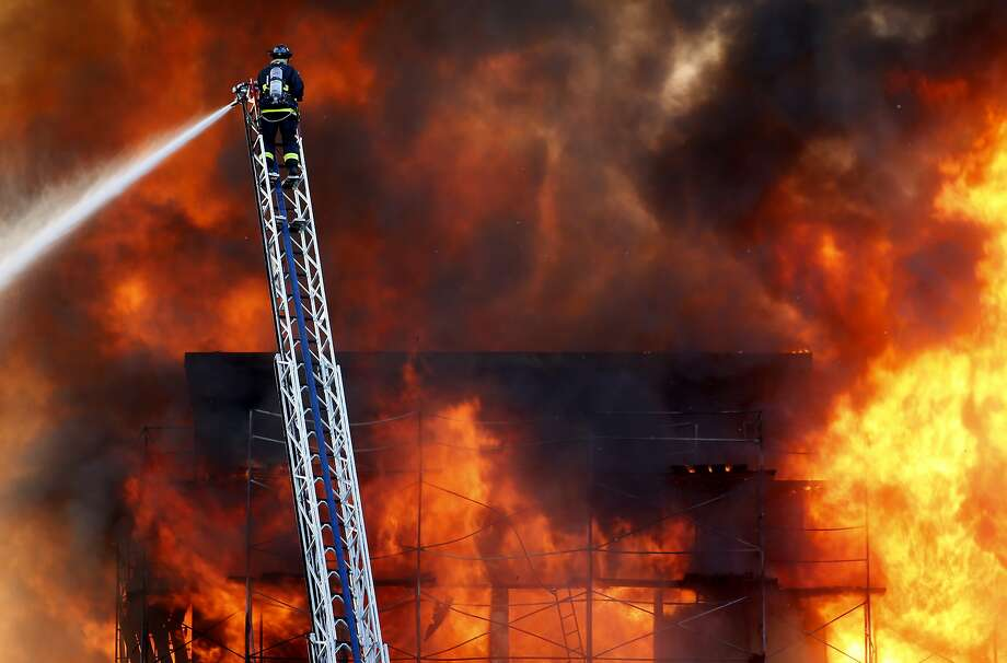 A San Francisco firefighter aboard an aerial ladder battles a five alarm fire at a fire in the Mission Bay area of San Francisco, Calif. on Tuesday March 11, 2014. Photo: Michael Macor, The Chronicle